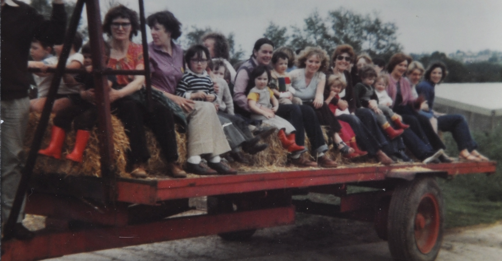 Mothers and children on a farm trailer, c. 1975