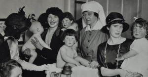 Baby weighing with visitors, c. 1925