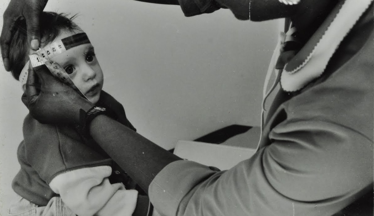 Nurse measuring size of child's head, c. 1975